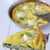 A slice of frittata with flecks of spinach inside and ricotta on the top