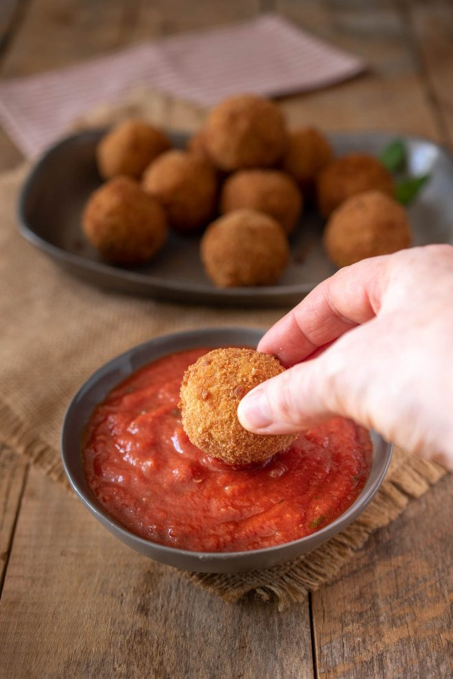 Dipping a risotto rice ball into tomato sauce