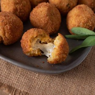 A risotto rice ball opened up to reveal the cheesy center