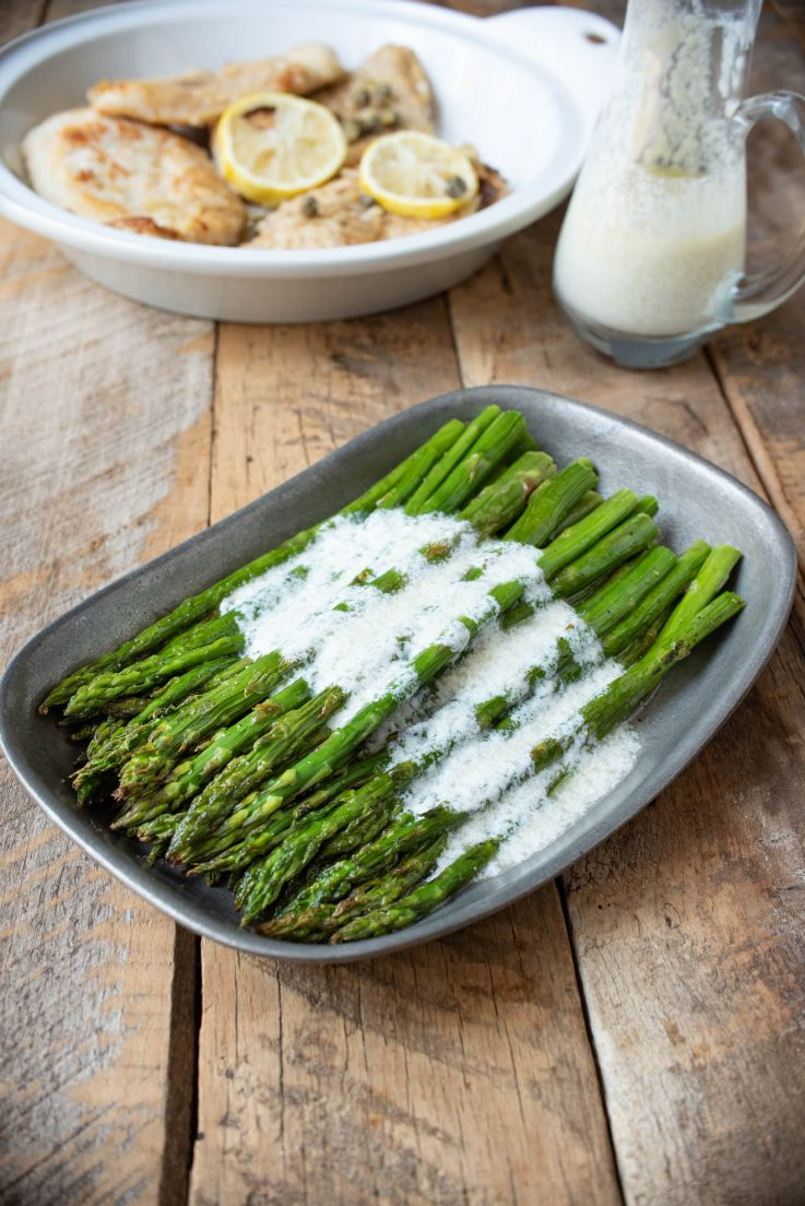 Asparagus served on a pewter plate with lemon ricotta sauce
