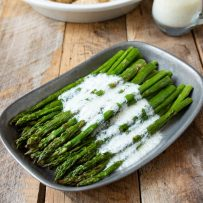 Asparagus spears on a grey plate drizzled with lemon ricotta sauce