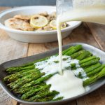 Pouring lemon ricotta sauce over roasted asparagus