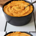 A black bowl filled with roasted carrot and parsnip puree with a spoon
