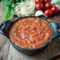 A black bowl filled with fresh tomato sauce