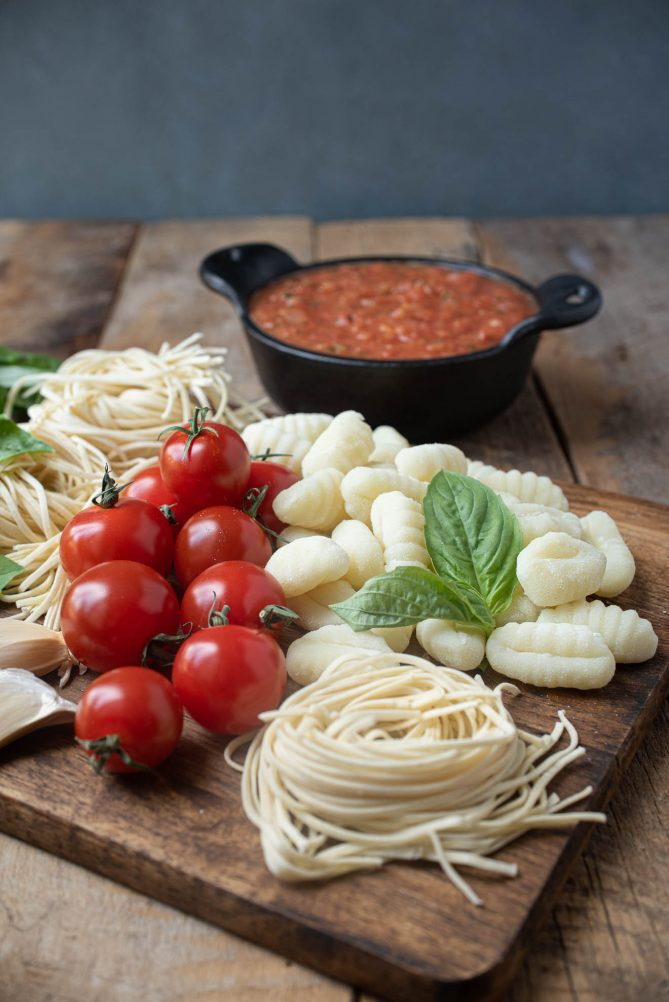 Fresh linguine, gnocchi, tomatoes and fresh basil on a board with tomato sauce in background