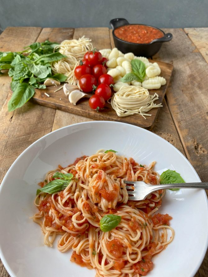 A bowl of pasta with fresh tomato sauce with a board of fresh pastas, tomatoes and basil behind