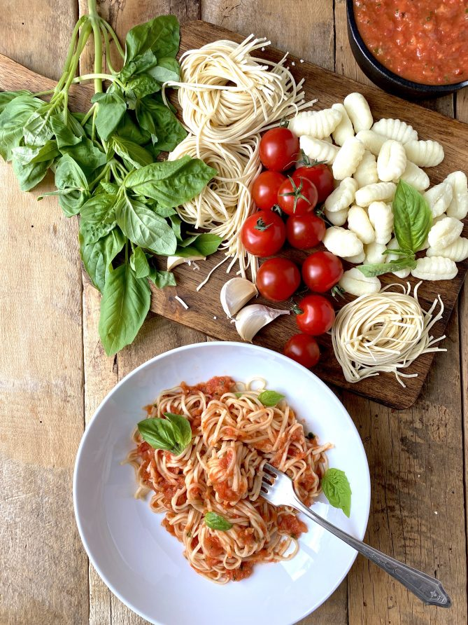 A display of fresh basil leaves, pasta and tomatoes viewed from overhead with a bowl of pasta and sauce