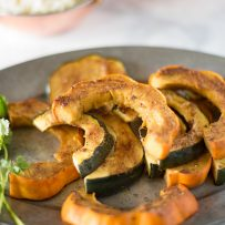 Slices of orange and green skinned acorn squash on a pewter plate