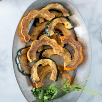 An oval plate of roasted acorn squash viewed from overhead