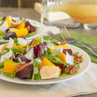 Pouring dressing onto a beet and arugula salad