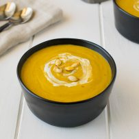 Roasted pumpkin and root vegetable soup garnished with pumpkin seeds and sour cream.