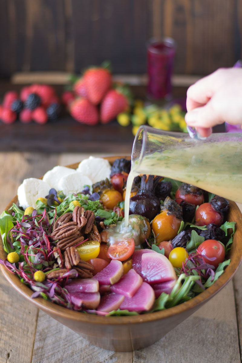 Pouring salad dressing on a large bowl of root vegetable salad