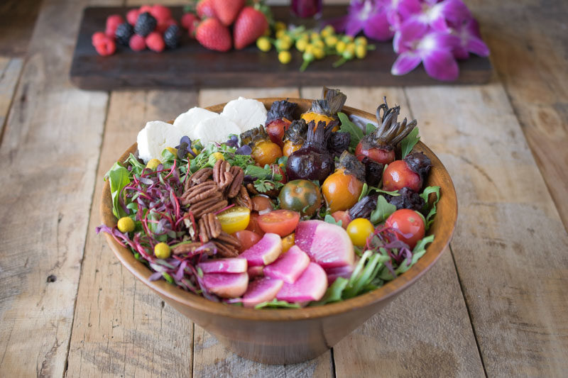 A large wooden bowl of colorful salad