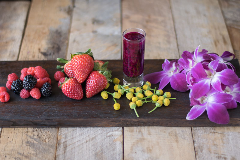 Colorful berries and edible flowers on a wooden board