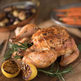 A whole roasted chicken on a cutting board with lemon halves