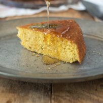 Drizzling honey onto a slice of Sage Cornbread