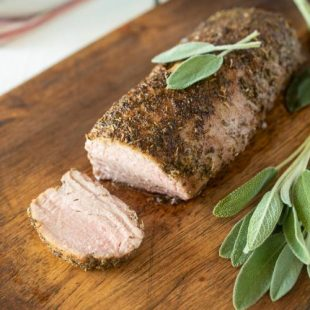 Sage rubbed pork tenderloin sliced and garnished with fresh sage
