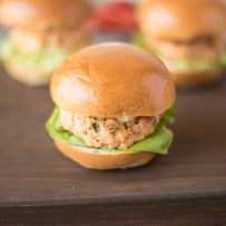 A salmon slider served on a brioche bun with lettuce