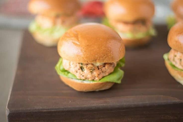 A salmon slider served on a brioche bun with lettuce