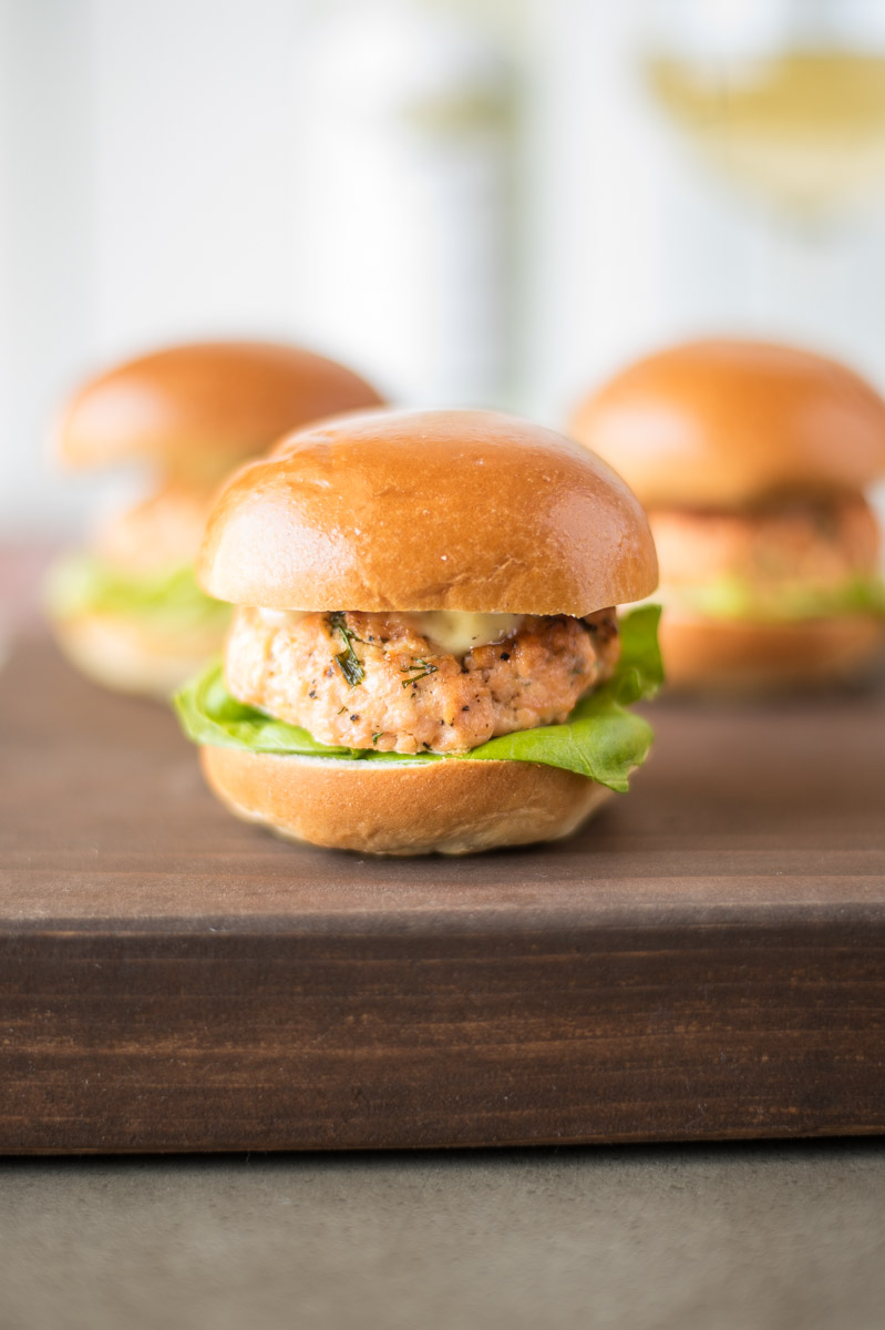 Salmon sliders with caper lemon mayonnaise are delicious, light, summery bites. Fresh salmon is mixed with chives, dill, Dijon mustard and lemon served on mini slider buns and topped with a flavorful mayonnaise.