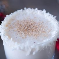 A closeup of Santa's Rum Spiced Milk showing the coconut rim and nutmeg garnish