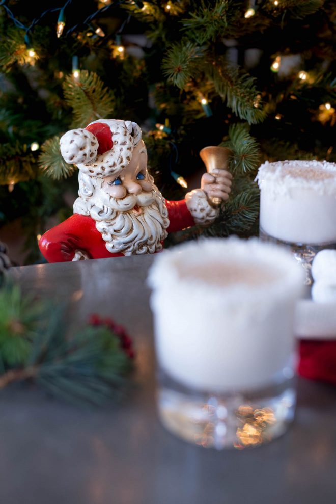 A ceramic Santa looking at his glass of Rum Spiked Milk