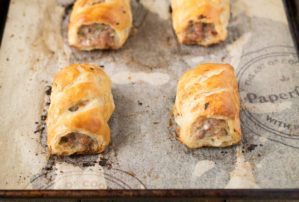 Homemade sausage rolls right out of the oven on a baking sheet