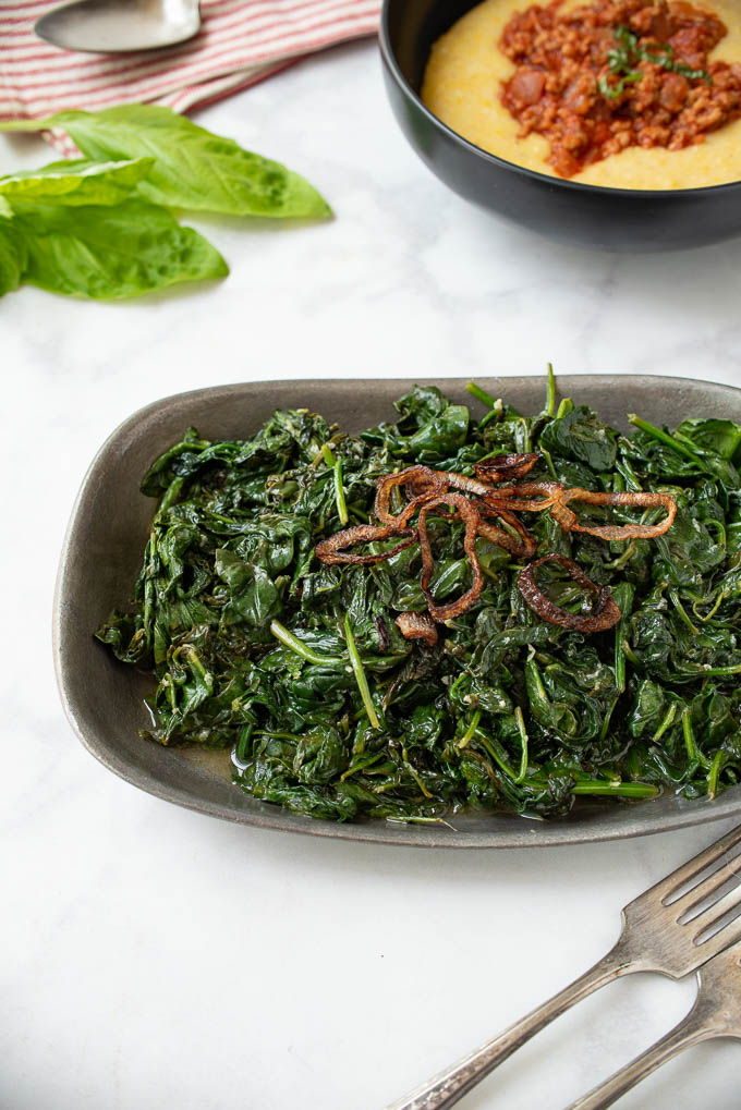 A pewter bowl filled with sauteed spinach topped with crispy shallots