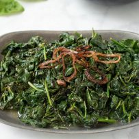 Sauteed spinach with crispy shallots in a grey bowl