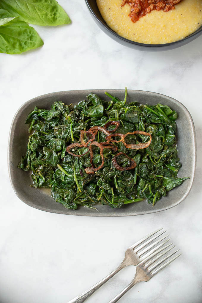 Vibrant green sauteed spinach from above with rings of crispy shallots