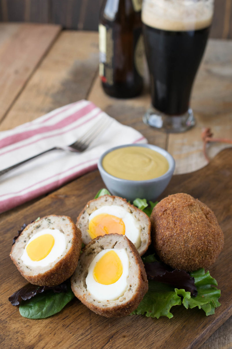 Scotch eggs on a board sliced open to show the egg inside