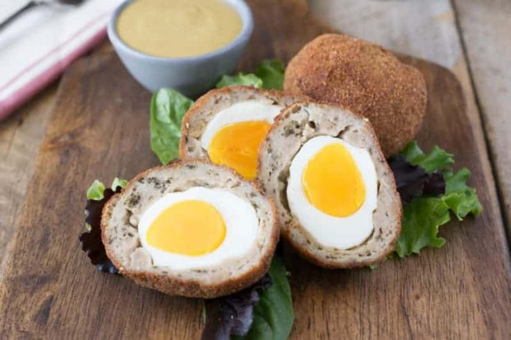 Cut open scotch eggs showing the sausage meat, yellow yolk and egg white