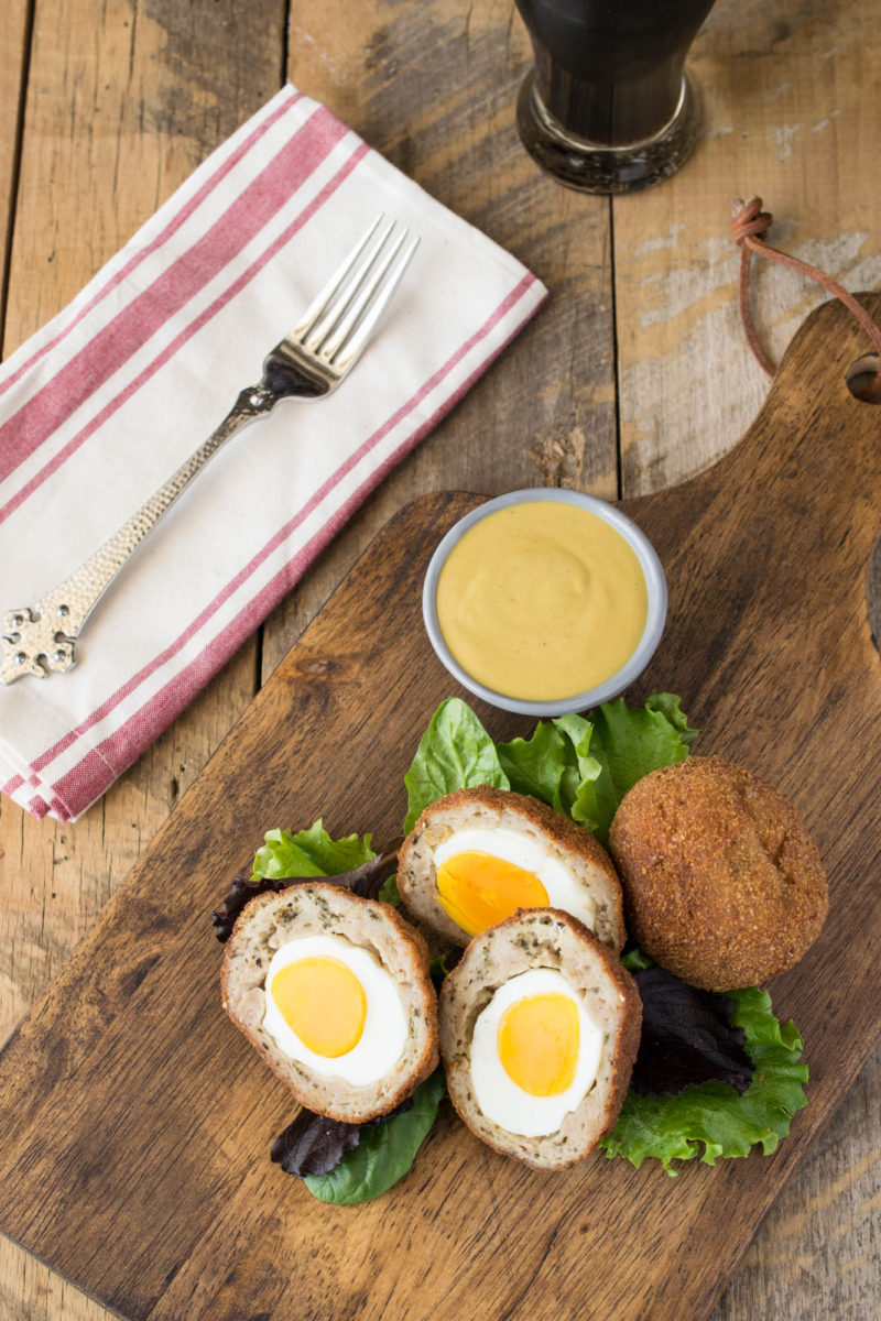 Scotch eggs from above on a board with mustard sauce