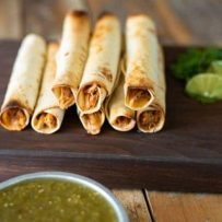Taquitos on a board with lime wedges and green salsa