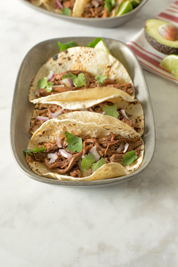 Slow cooker barbacoa tacos. Beef roast is slowly cooked in a homemade guajillo chile pepper sauce until it is fall apart and shredded, served simply in soft tortillas with red onion and cilantro.