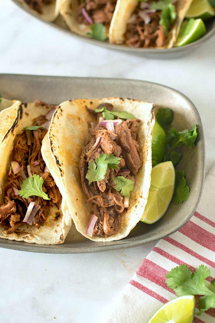 Slow cooker barbacoa tacos lined up on a pewter plate with fresh limes