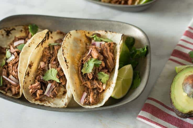Shredded beef in a soft taco served with fresh cilantro