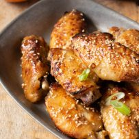 A closeup of an orange chicken wing sprinkled with sesame seeds