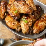 Orange chicken wings in a bowl and dipping a wing in orange sauce