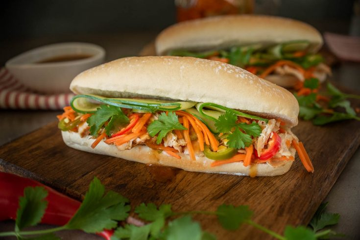 A soft roll is filled with shredded chicken, carrot slaw, cucumber and cilantro