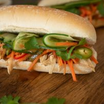 A closeup showing the banh mi filling of shredded chicken, shaved cucumber, carrot slaw and cilantro