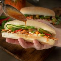 Drizzling the delicious sauce on banh mi