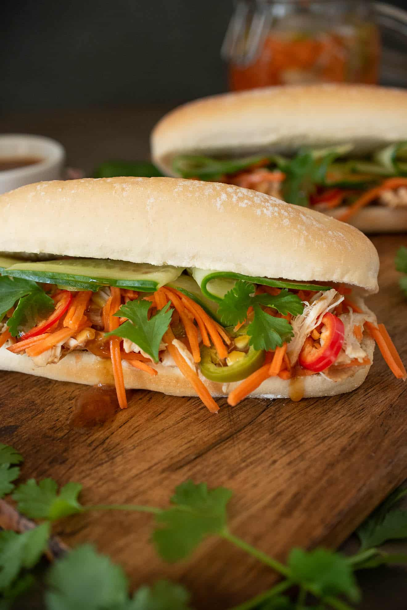 Shredded chicken, carrot slaw, cilantro and cucumber spilling out of a banh mi sandwich