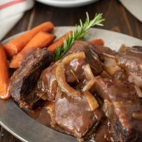 Short ribs and gravy on a plate with carrots and rosemary