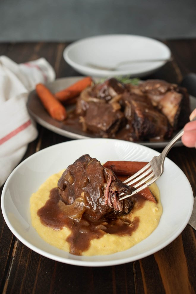 Beef short ribs on polenta with carrots on a white plate