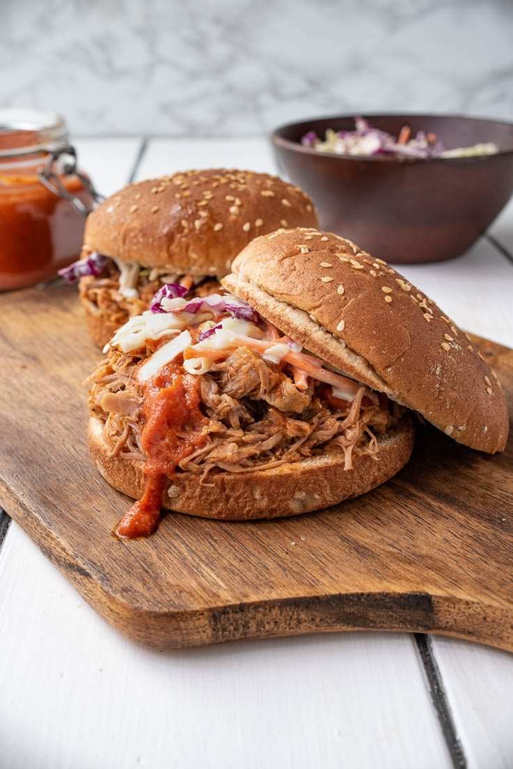 A pulled pork sandwich on a board topped with coleslaw