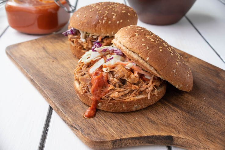 A pulled pork sandwich with the top bun tilted showing the meat topped with coleslaw