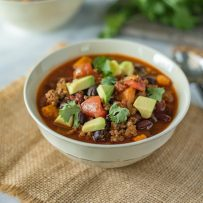 Slow cooker beef and sweet potato chili served in a white bowl with a spoon