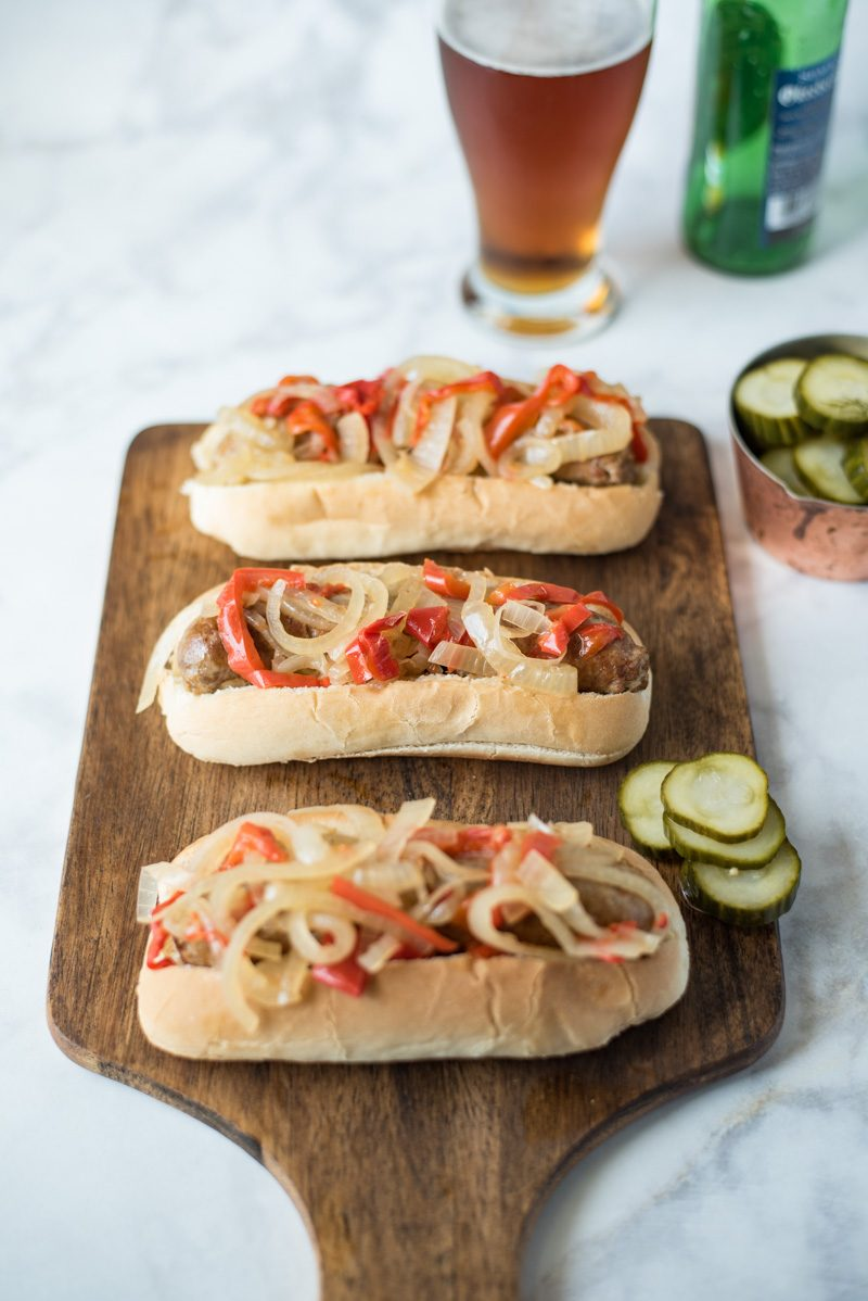 low cooker beer bratwurst with onions and peppers are the perfect, easy cookout meal for a crowd. Brats are slow cooked in German beer along with onions and peppers, pile onto a bun and you're set.