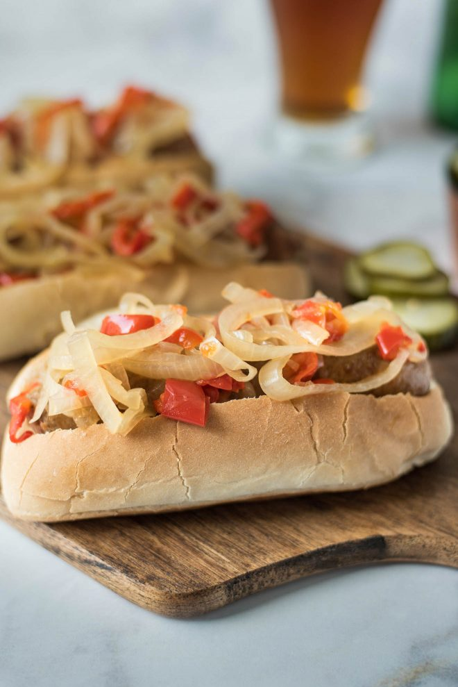 Onions and peppers piled on top of a bratwurst sandwich